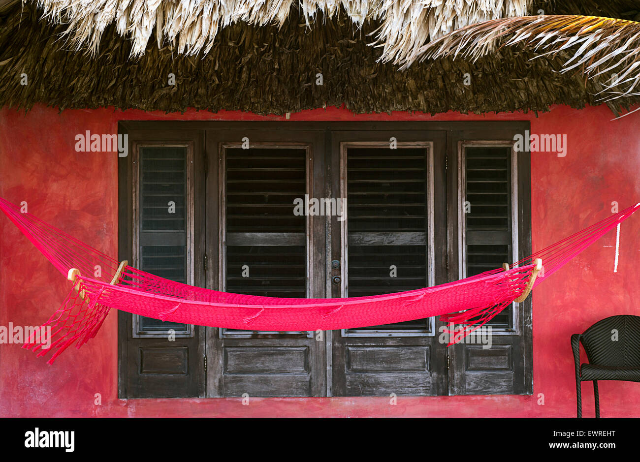 A hammock against a red wall at the Mata Chica resort in Belize. - Stock Image