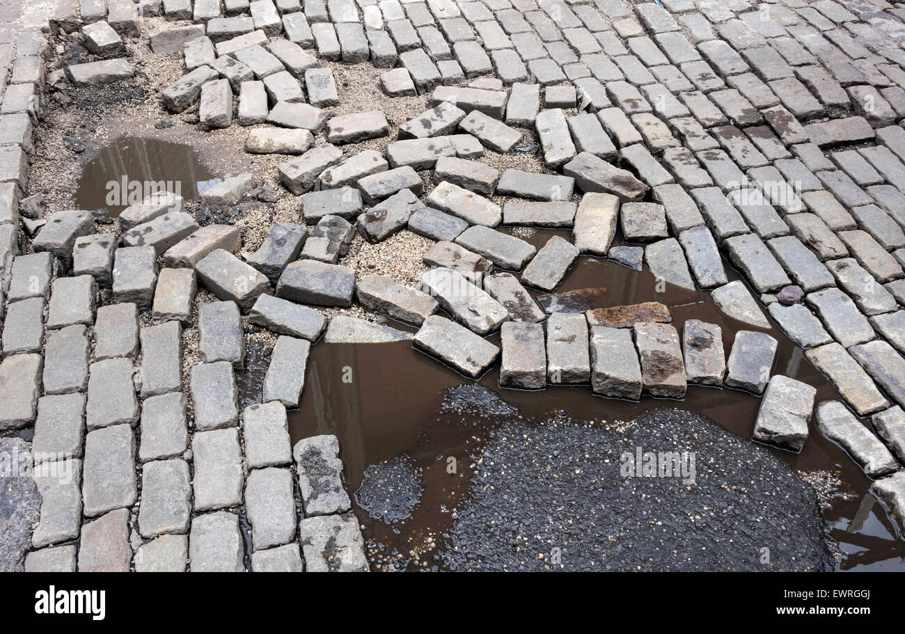Broken surface of cobblestones on a street in Soho in New York City shows neglect and disrepair - Stock Image