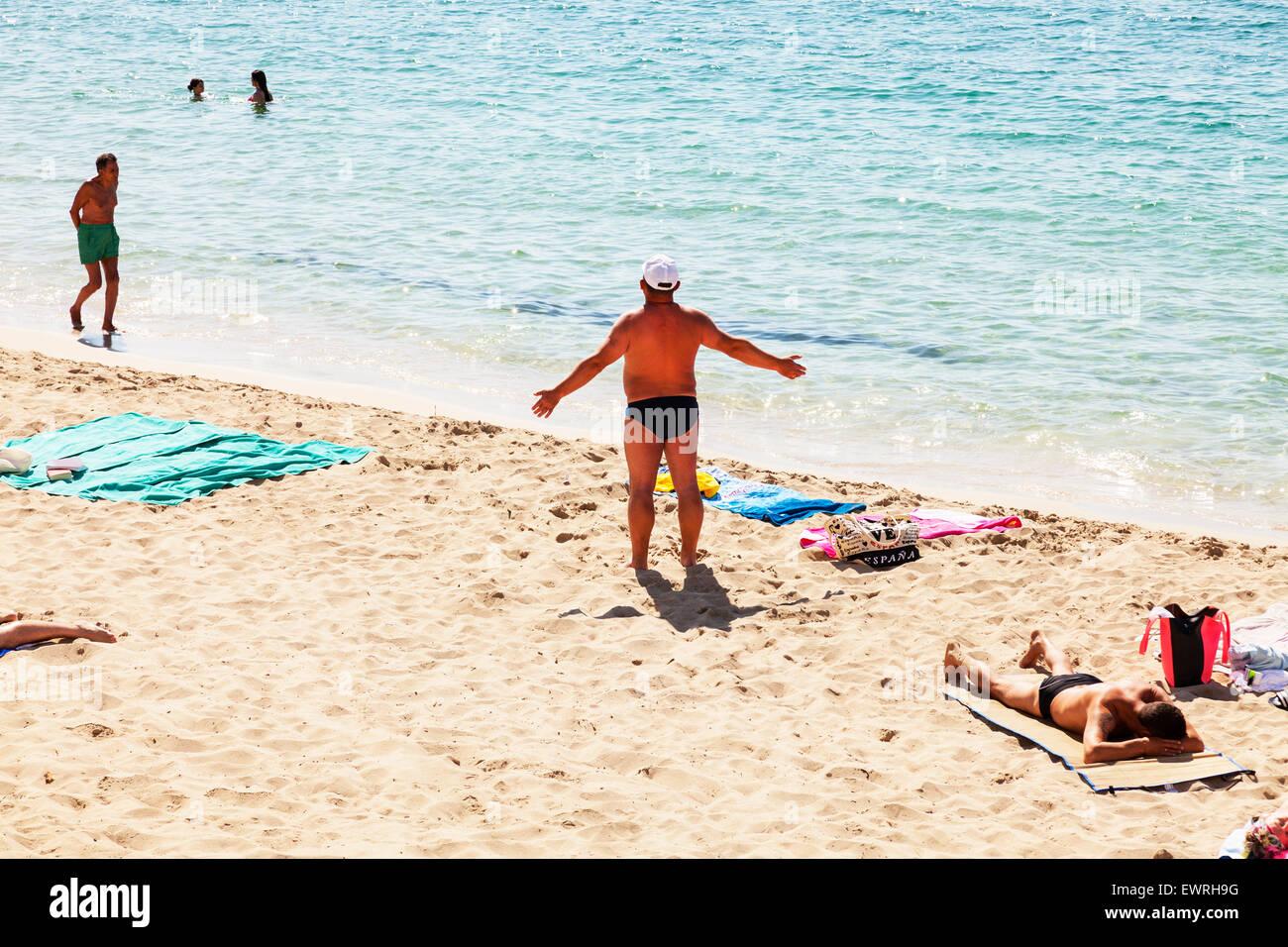 Sunbather sunbathing sun worshiper worshipper bather beach coast Santa Eulalia Del Rio Ibiza Spain Spanish resort - Stock Image