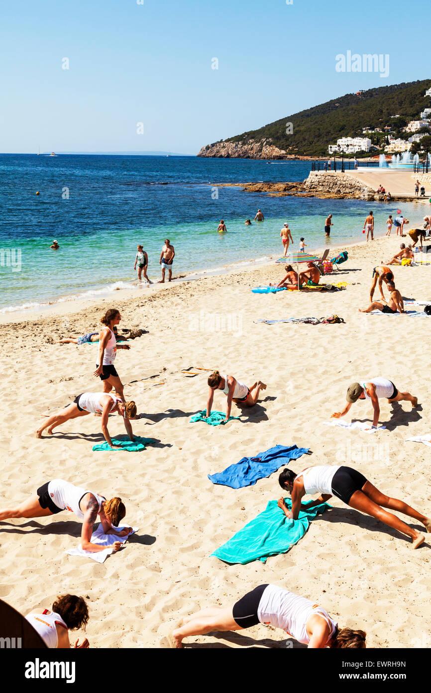 Keep fit on beach lessons yoga pilates press ups pressups health healthy fitness Santa Eulalia Del Rio Ibiza Spain - Stock Image