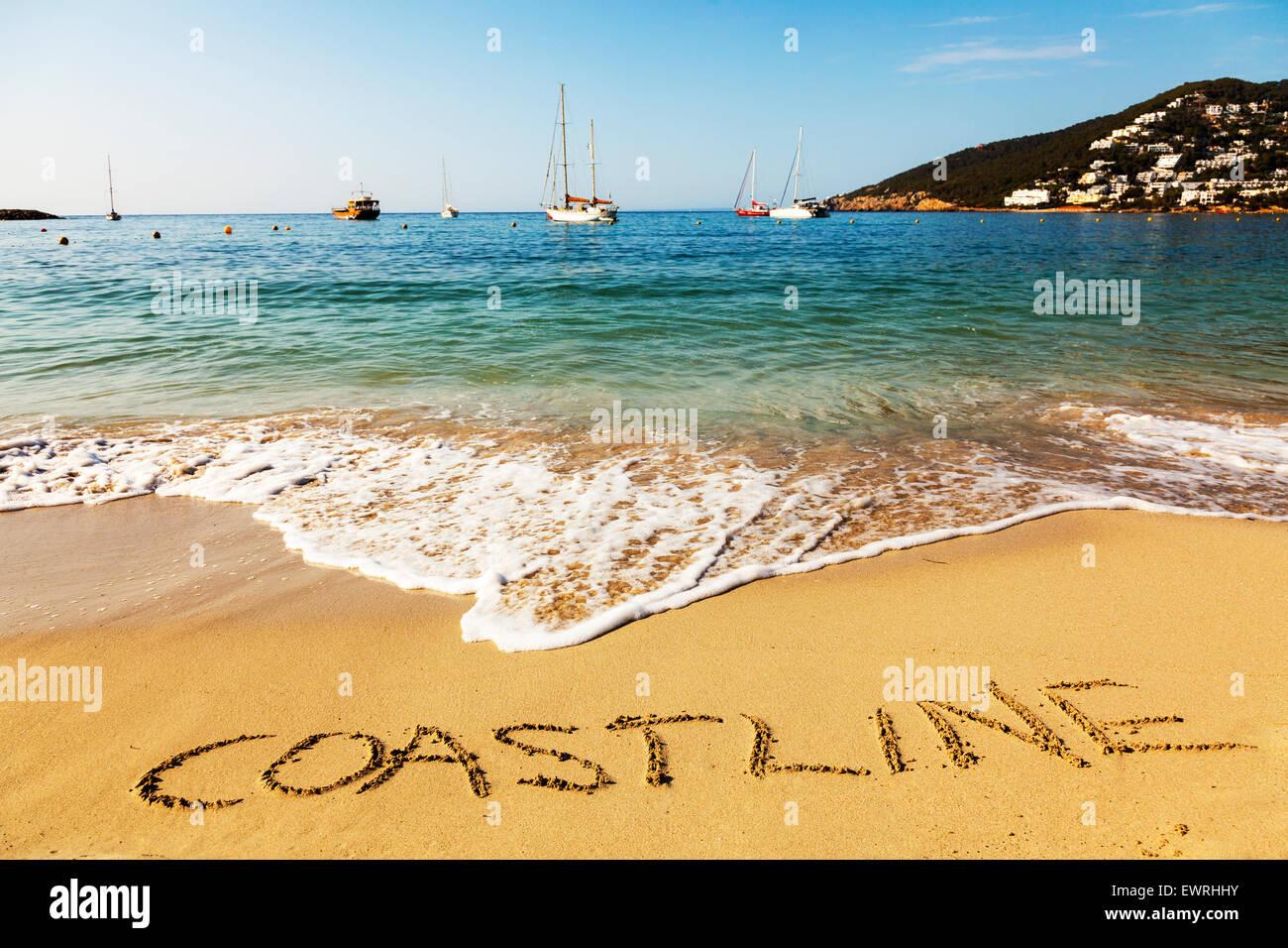 Coastline word in sand written on beach Spanish fun resort seas coast coastlines holidays vacations trips trip getaway - Stock Image