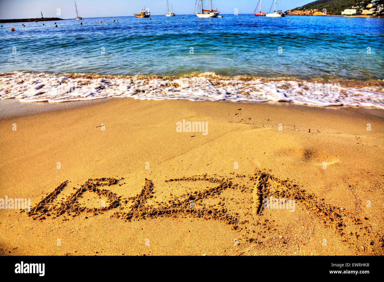 Ibiza word in sand written on beach resort sea coast coastline holiday getaway Spain Santa Eulalia Spanish summer - Stock Image