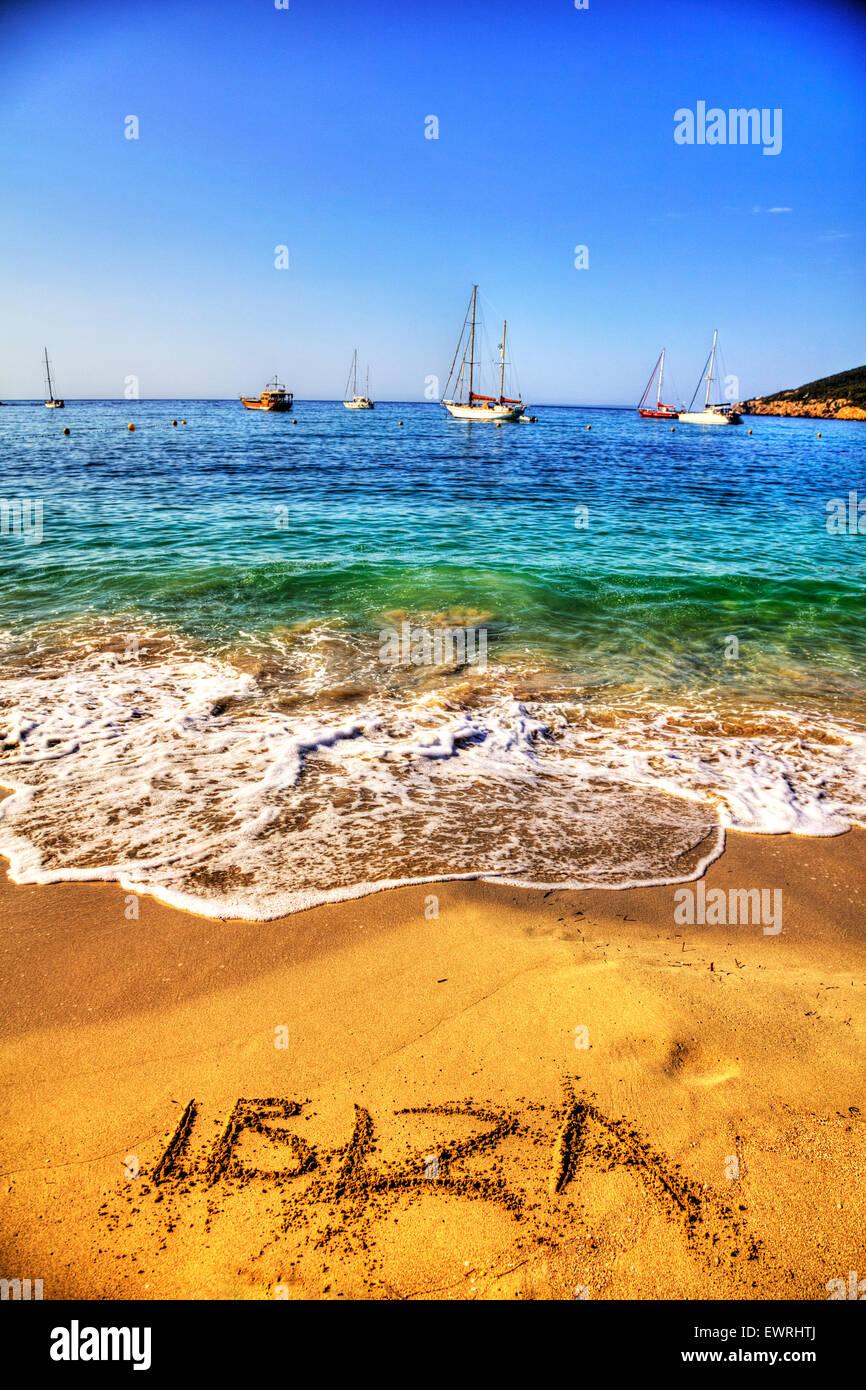 Ibiza word in sand written on beach resort sea coast coastline holiday getaway Spain Santa Eulalia Spanish summer - Stock Image