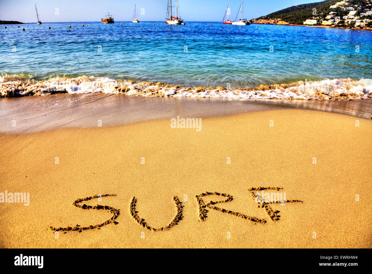 Surf word in sand written on beach sea coast coastline holiday getaway Ibiza Spain Santa Eulalia Spanish - Stock Image