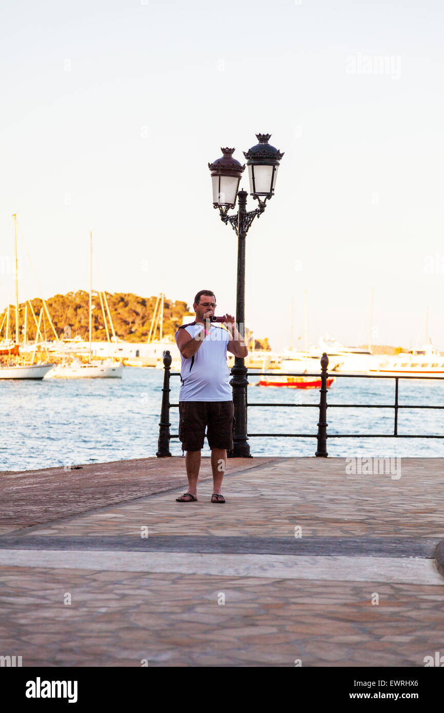Man videoing using camcorder to video filming film filmaker maker  Ibiza Spain Spanish resort - Stock Image