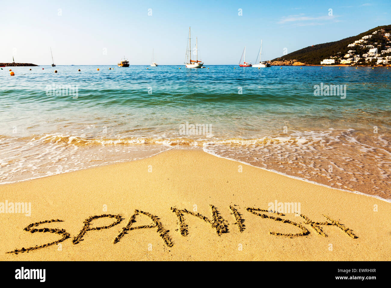Spanish word in sand written on beach coast coastline holiday getaway sea Ibiza Spain Santa Eula - Stock Image