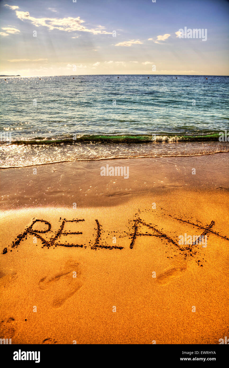 Relax in sand word written on beach coast chill holiday getaway sea coastline Ibiza Spain Spanish Santa Eulalia - Stock Image