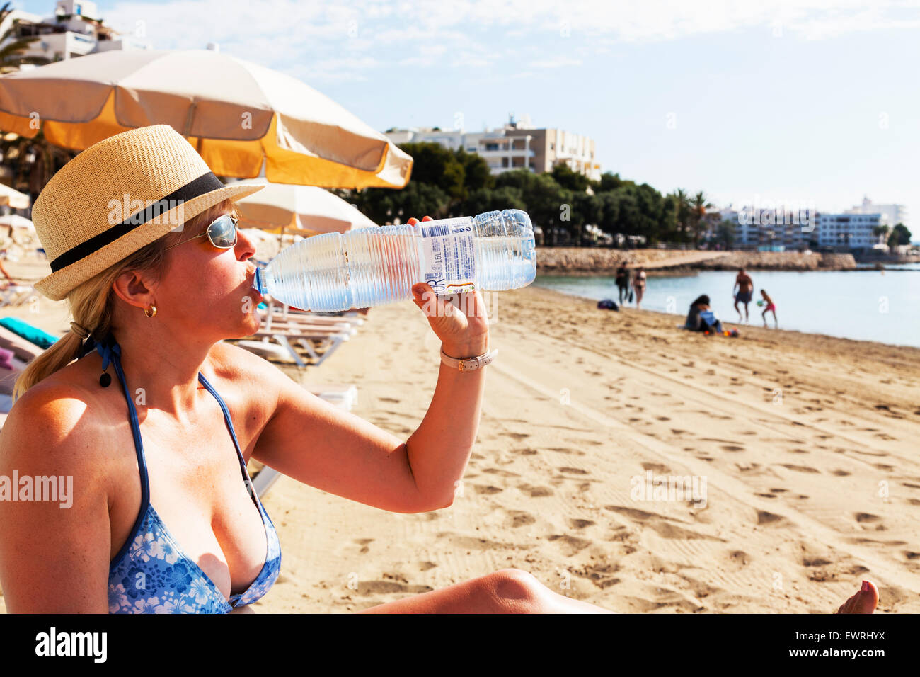 drinking drink water from bottle hydrating rehydrate rehydrating sun sunny summer thirst thirsty Ibiza Spain Spanish - Stock Image