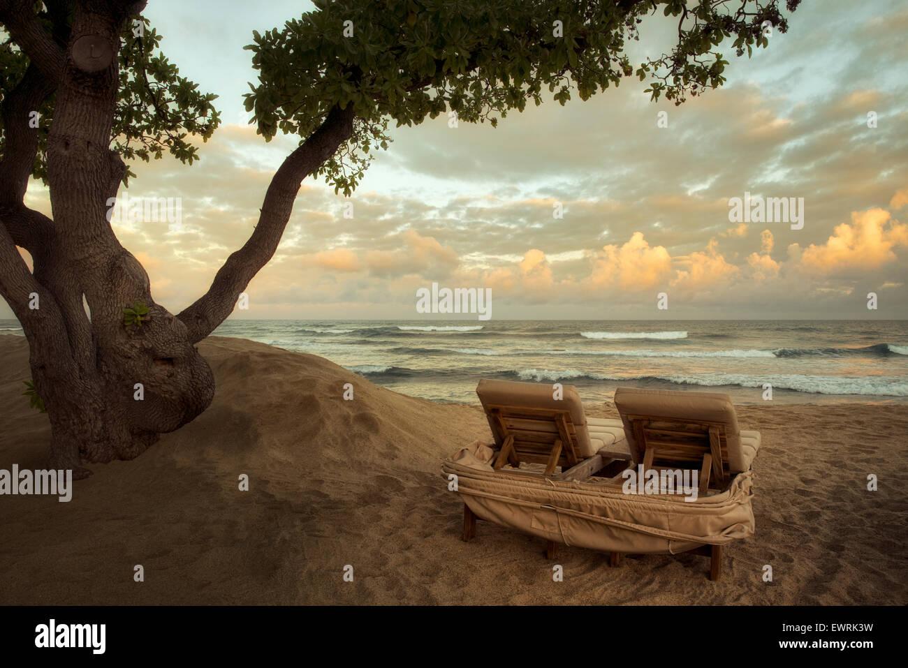 Sunrise and waves with beach chairs. Hawaii, The big Island. Stock Photo