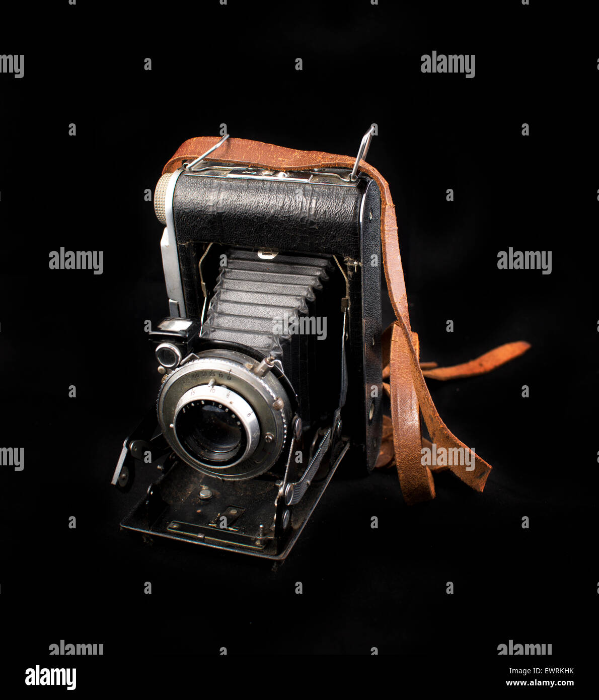 Vintage analog photo camera with bellows isolated on black background - Stock Image