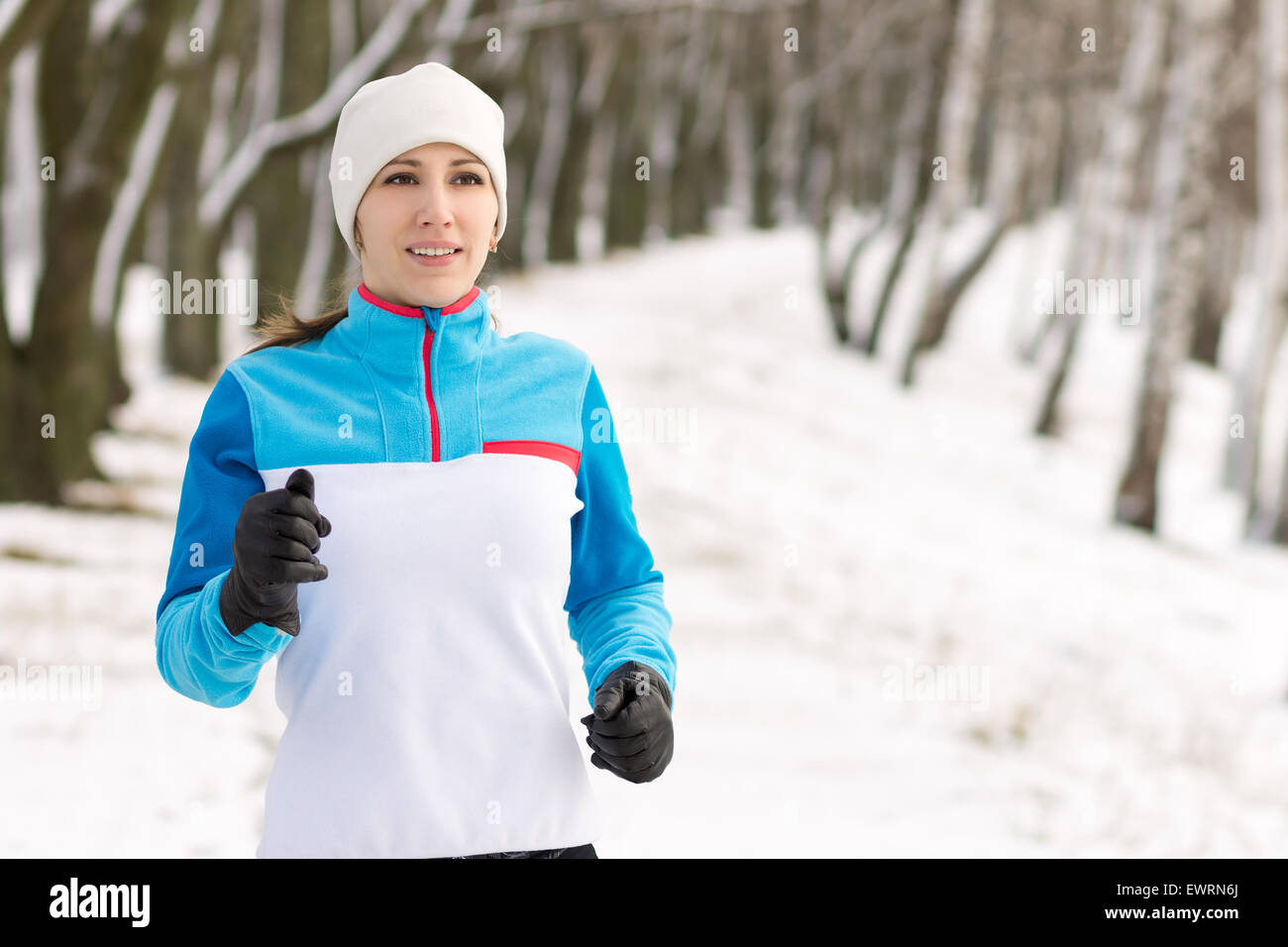 Young smiling athlete woman jogging in winter park. Pretty girl running at winter outdoor with copy space. - Stock Image