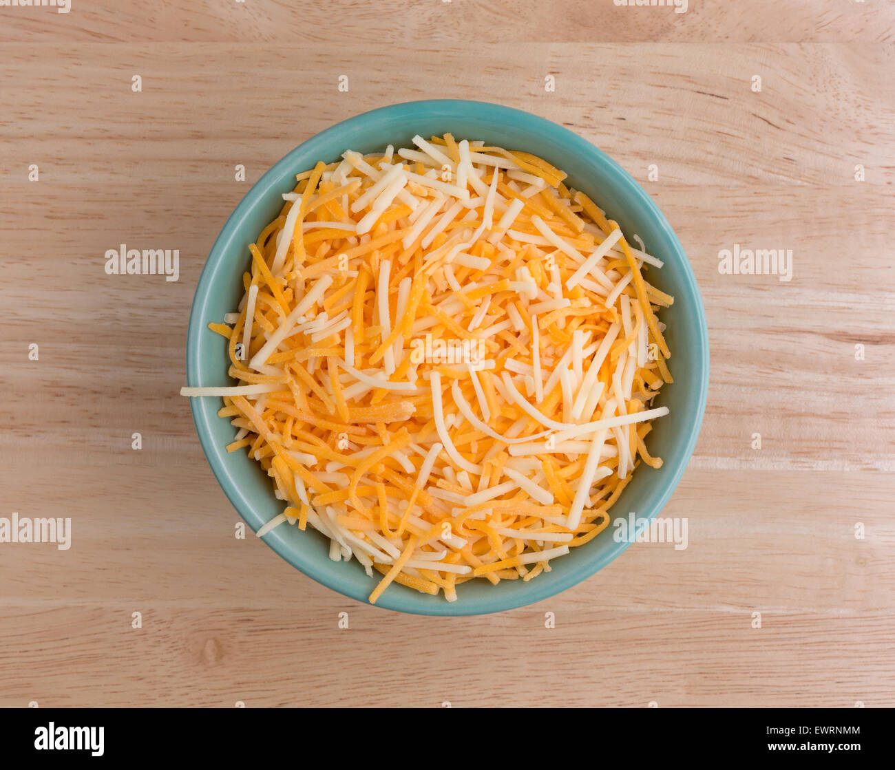 Top view of a small bowl filled with shredded white cheddar, sharp cheddar and mild cheddar cheeses atop a wood - Stock Image