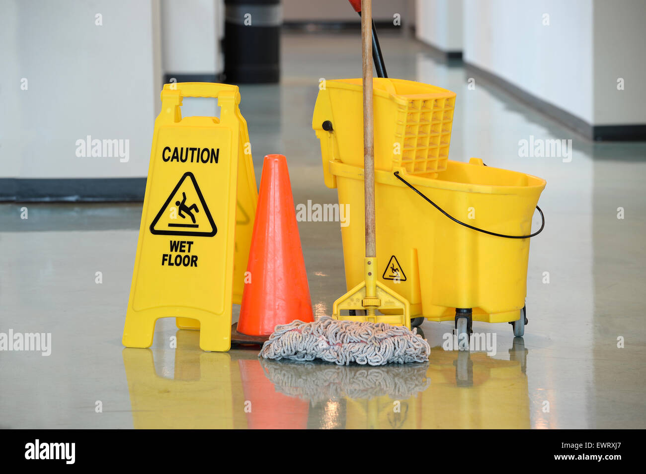 Caution sign with mop and bucket on office floor - Stock Image