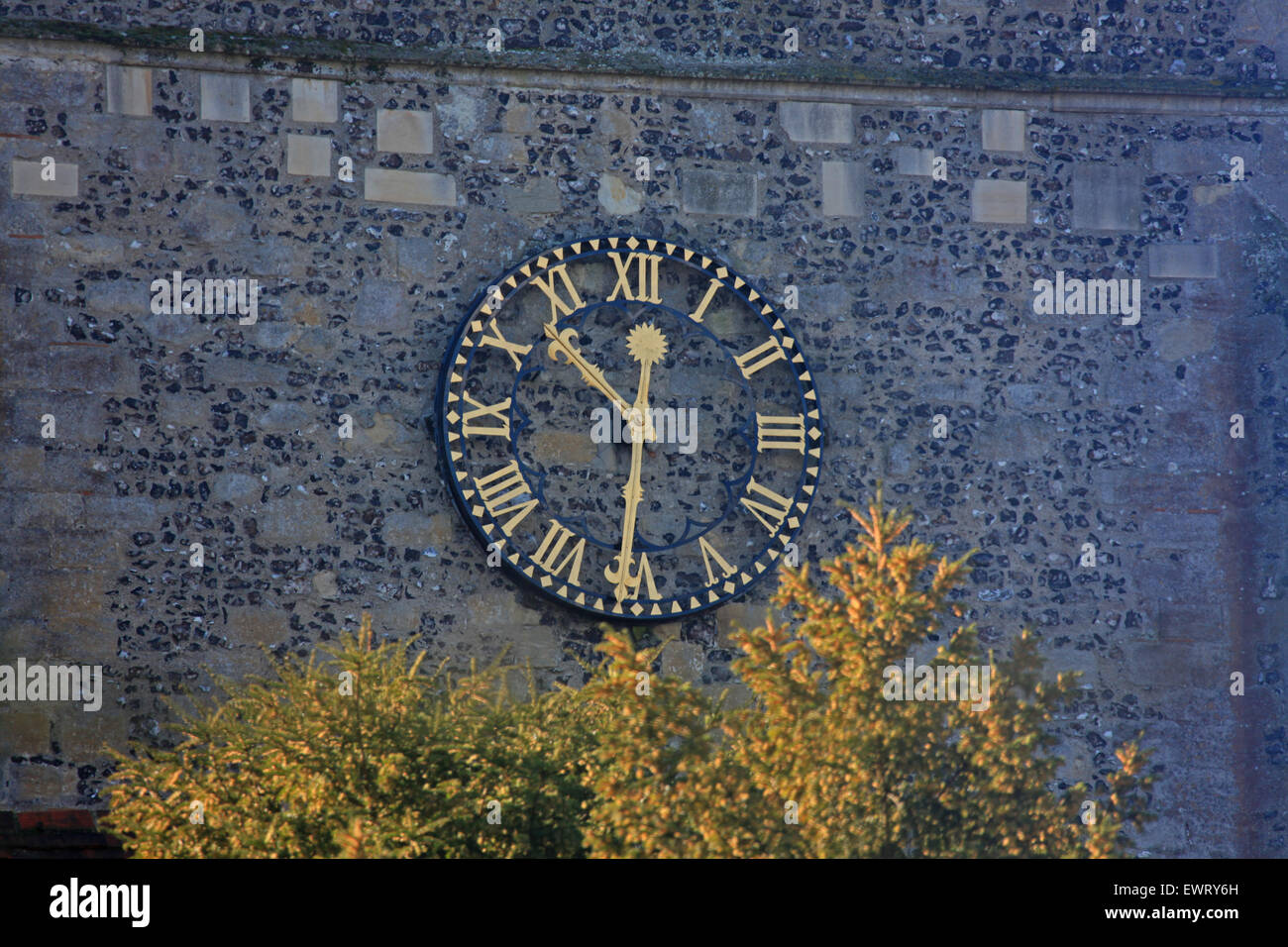 A church wall clock with Gold numbers and hands on a flint and block background. - Stock Image