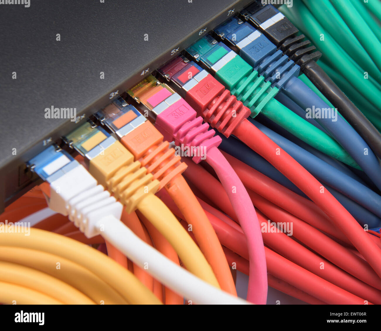 Colorful network cables connected to a switch - Stock Image