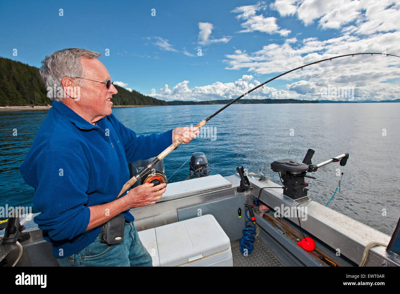 Senior retired man fishing with fishing rod in his hands off Northern Vancouver Island in British Columbia, Canada. - Stock Image