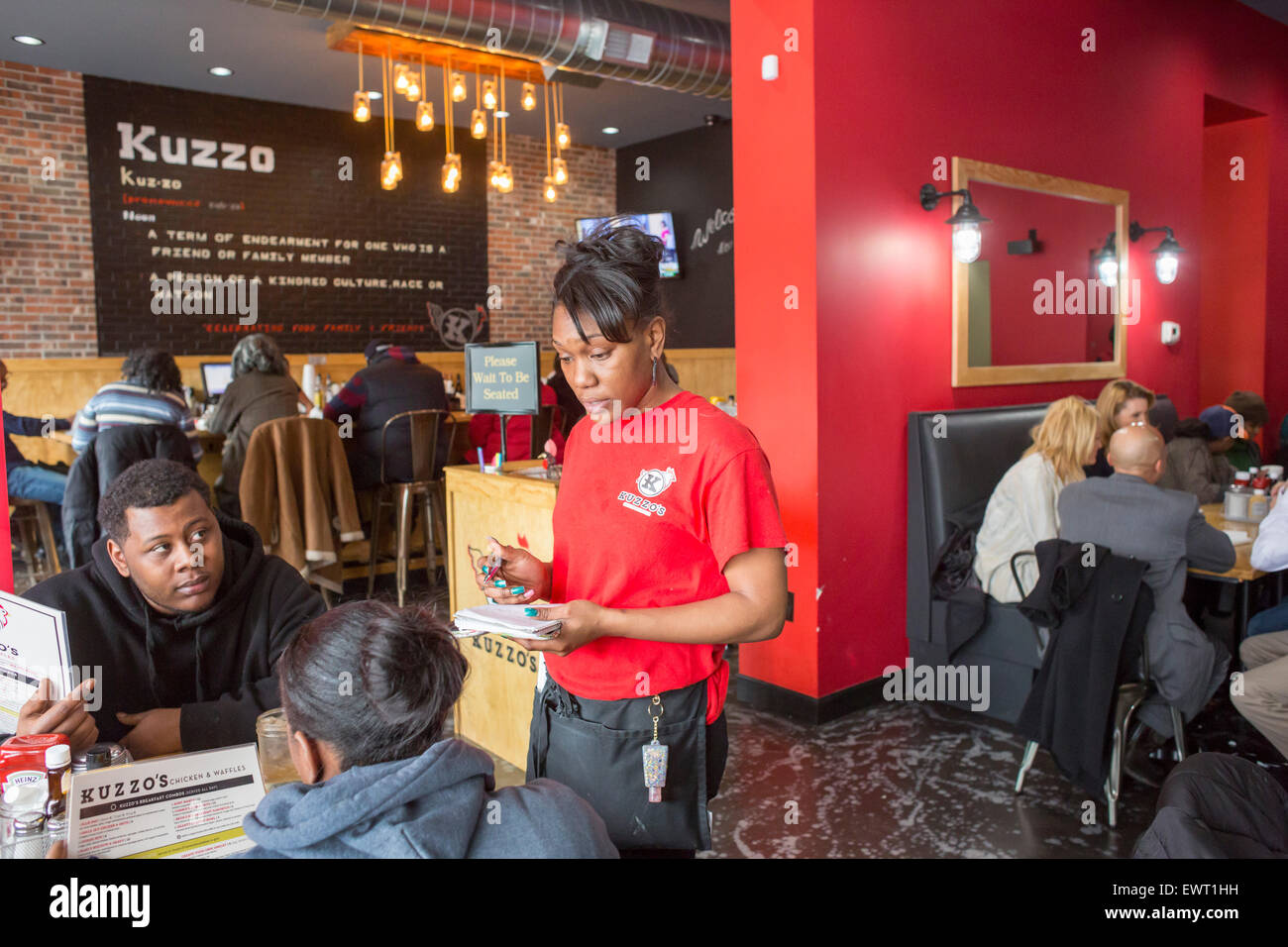 Detroit, Michigan - A server takes an order at Kuzzo's Chicken & Waffles. - Stock Image