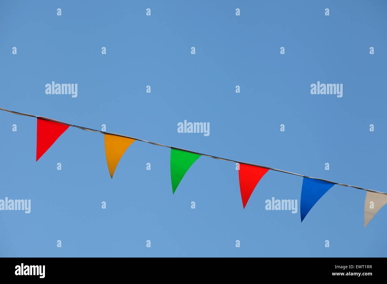 Coloured bunting flags against a blue sky background - Stock Image