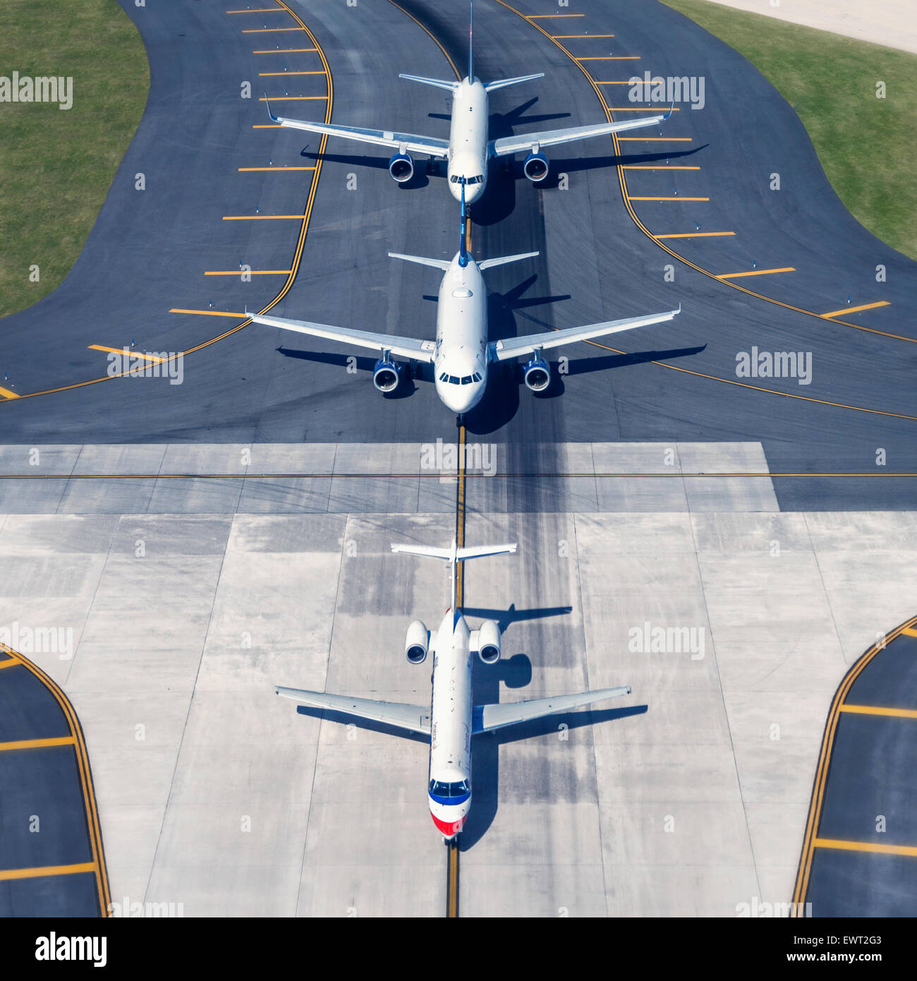 Airplanes on runway in line waiting to take-off. - Stock Image