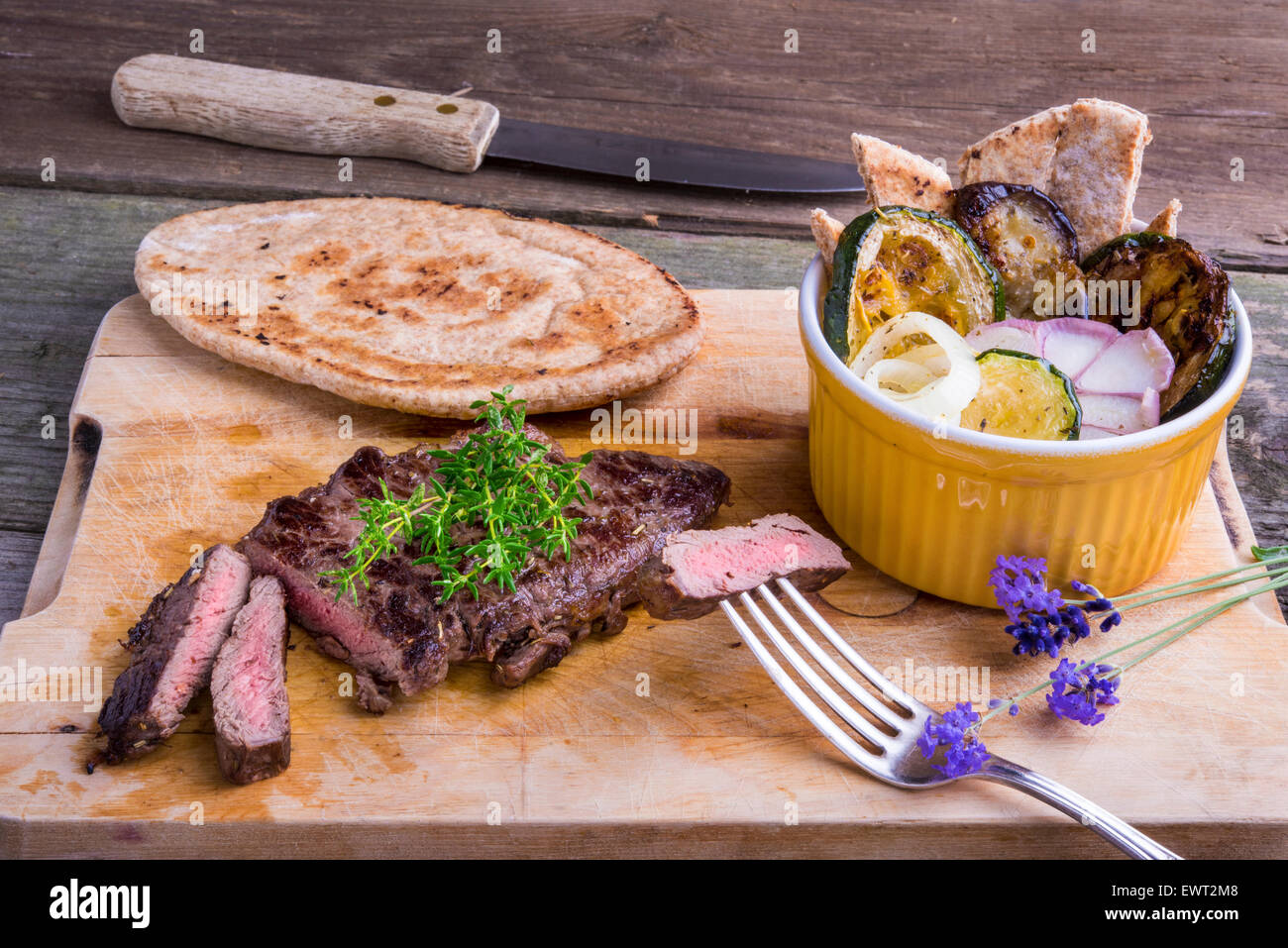 Provencal style horse meat entrecote steak with ratatouille and flat bread served on a wooden board decorated with - Stock Image