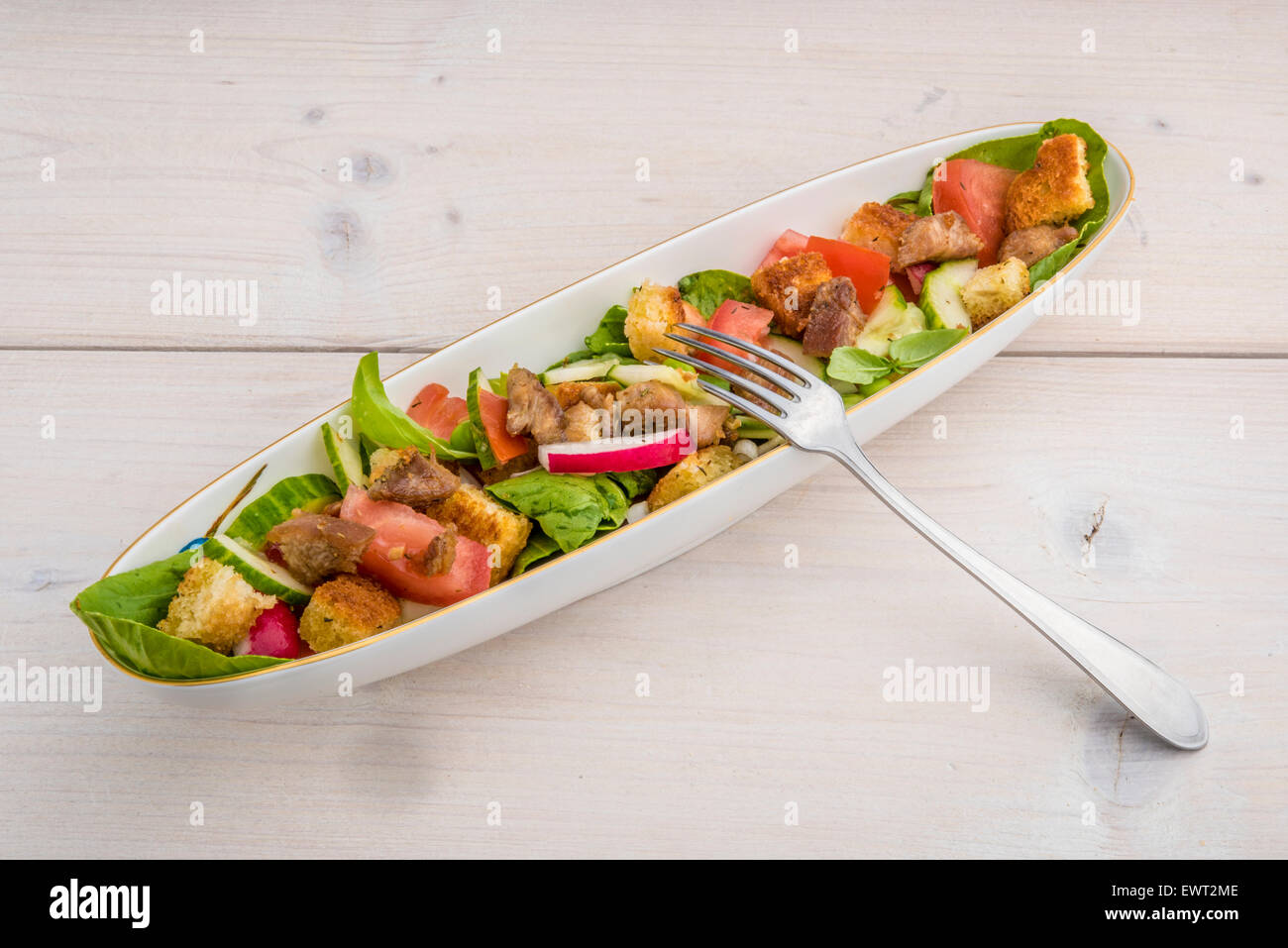 Fresh salad with bok choy, tomatoes, radiches, cucumber, basil, croutons and grilled turkey meat. - Stock Image