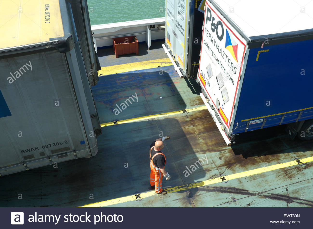 A stevedore guiding a shunter, who's loading lorry semi-trailers on to a Stena Line ferry, at Hoek van Holland, - Stock Image
