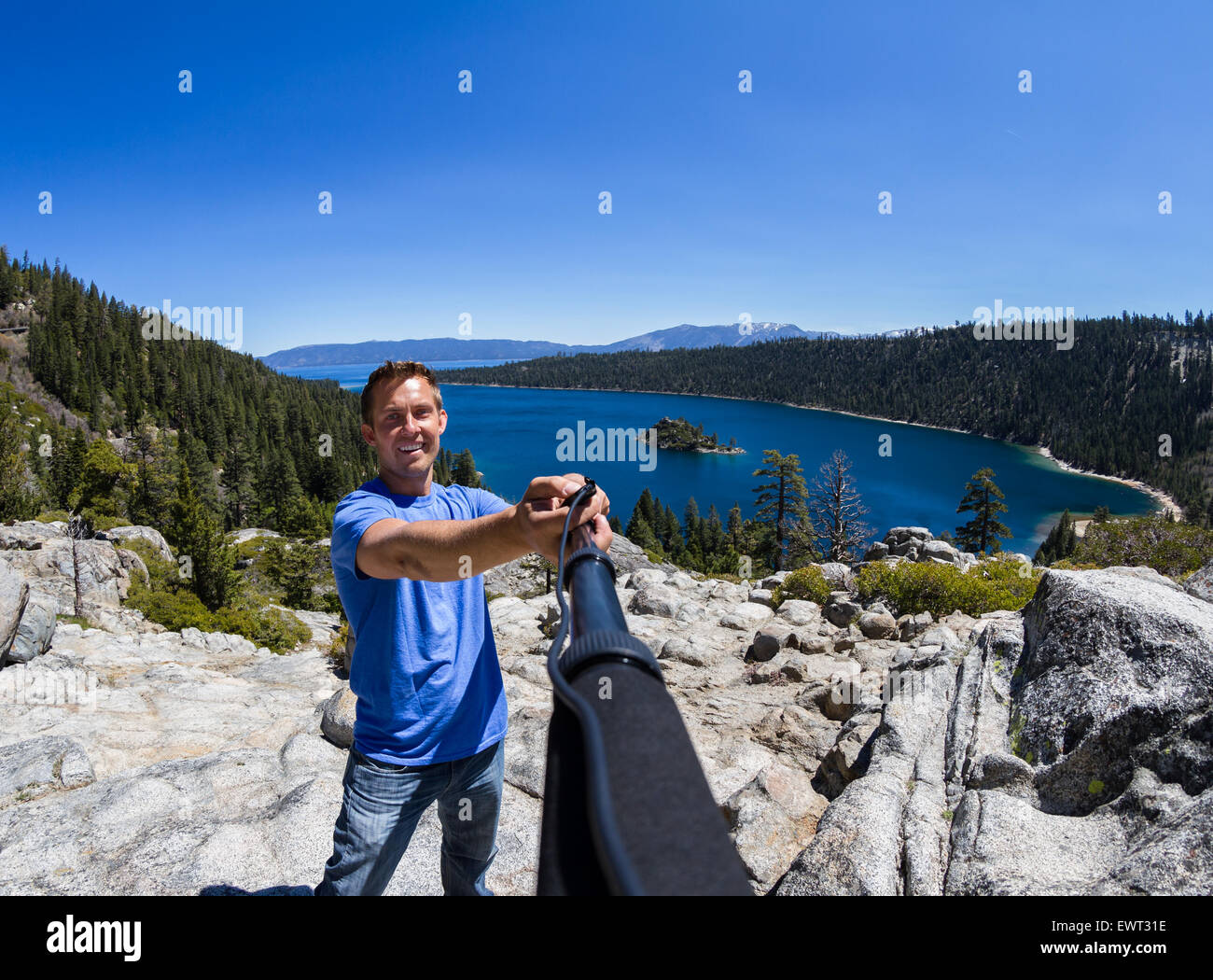 young man akin a selfie with Fannette Island and Emerald bay in the background - Stock Image