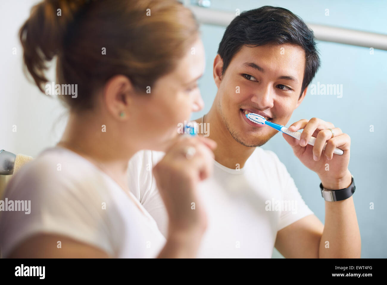 Young couple living together, washing teeth in bathroom in the morning. The woman looks happily at her boyfriend. - Stock Image
