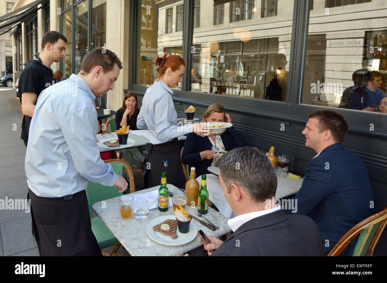 LONDON - MAY 14 2015:Waiters serving food and drinks to people dining in a restaurant in London England UK.The average - Stock Image