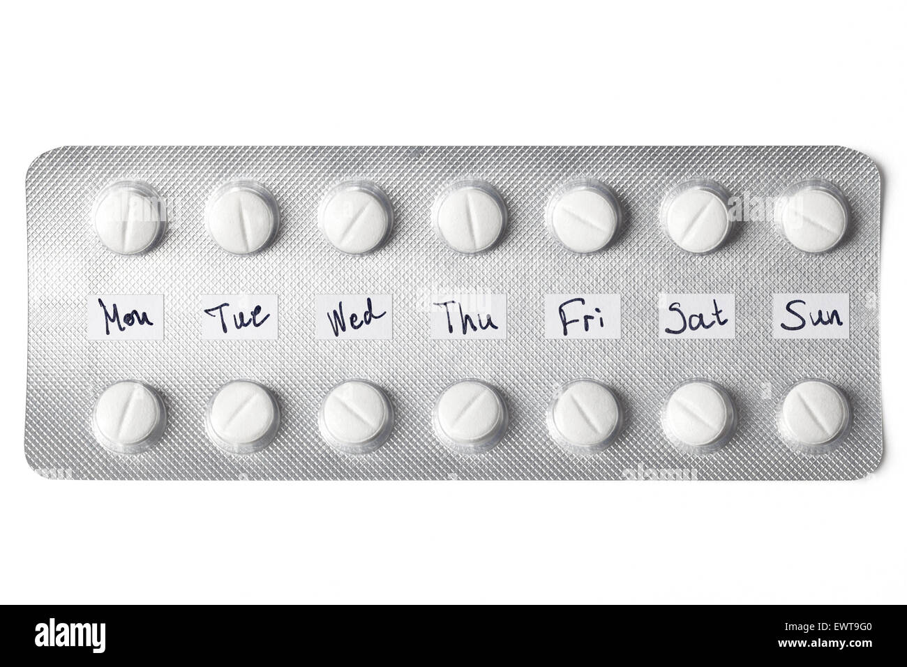 Blister with pills tagged for daily intake isolated on white. - Stock Image