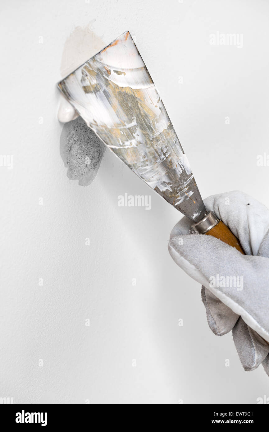 Worker is plastering a wall by spatula and plaster - Stock Image