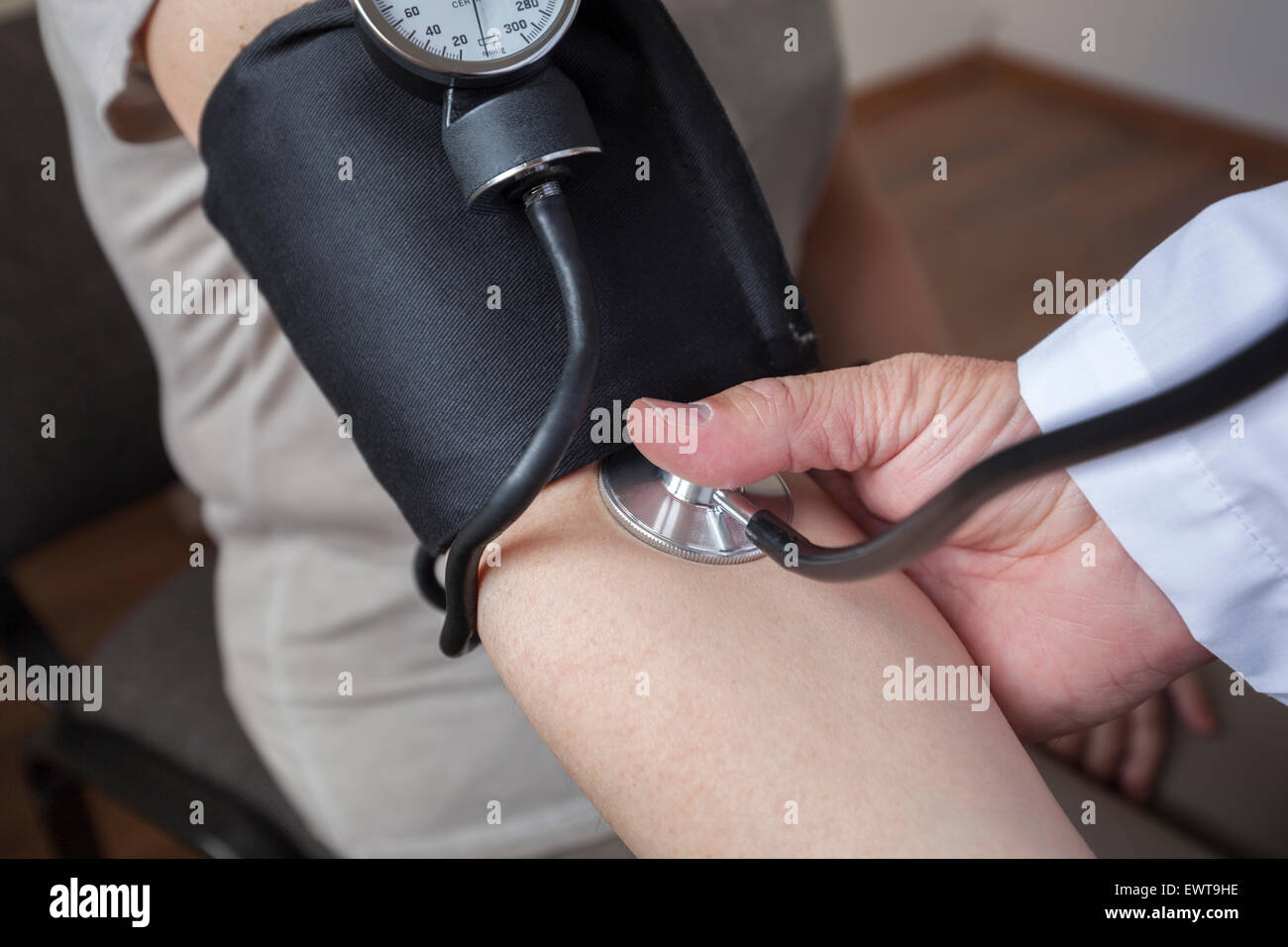 Doctor cardiologist is measuring a blood pressure of woman in the consulting room. He is starting and will be careful - Stock Image