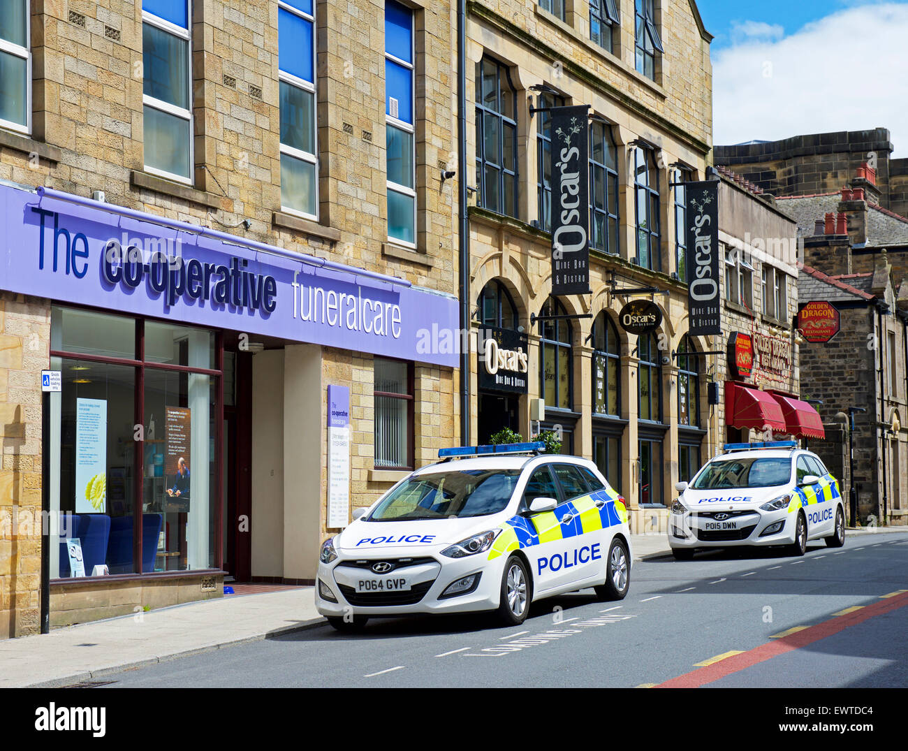 Co-Operative Funeral Parlour, and two parked police cars, in Lancaster, Lancashire, England UK - Stock Image
