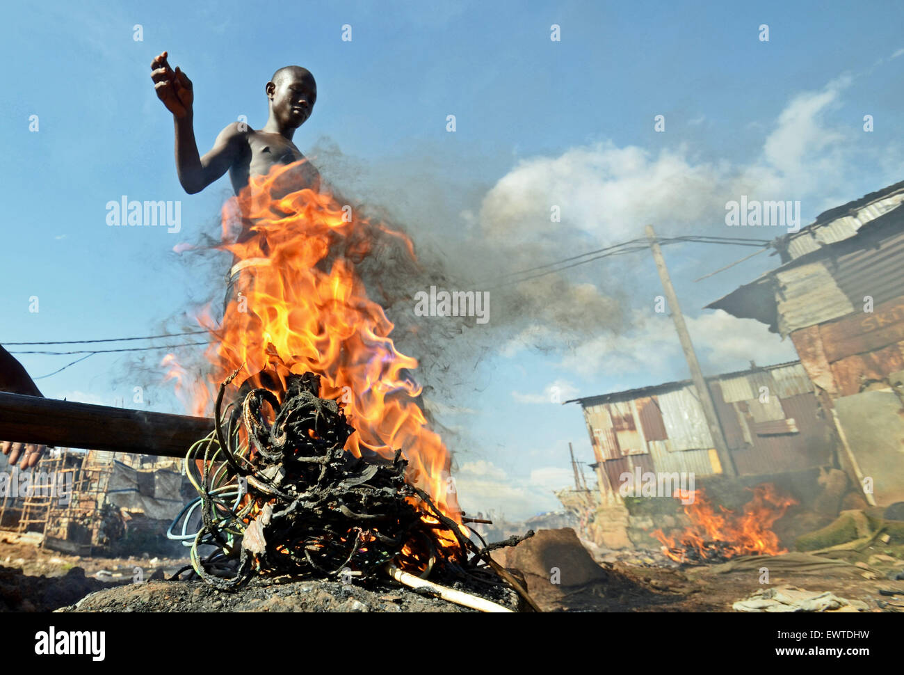 A boy burns electrical cables to extract the copper wire in Kroo Bay slum, Freetown, SierraLeone - Stock Image