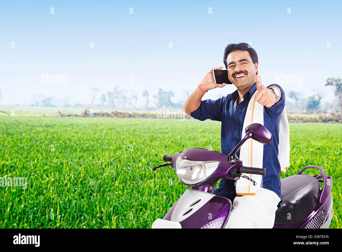 284f8cf486 1 South Indian man farm Riding Scooty and talking Cell Phone Stock ...