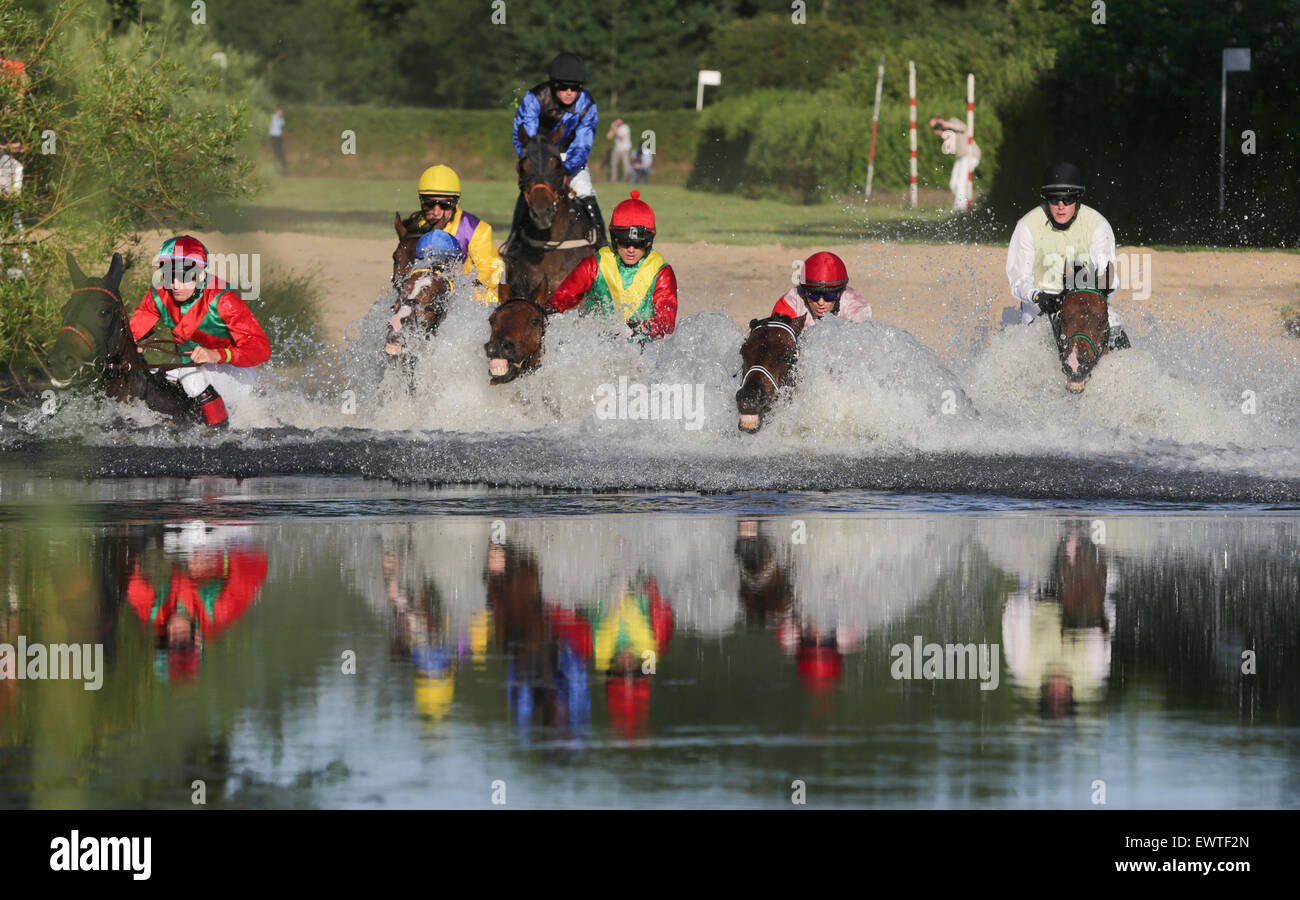 Hamburg, Germany. 30th June, 2015. A field of jockeys chase their horses through a pond during the Alpine Motorenoel - Stock Image