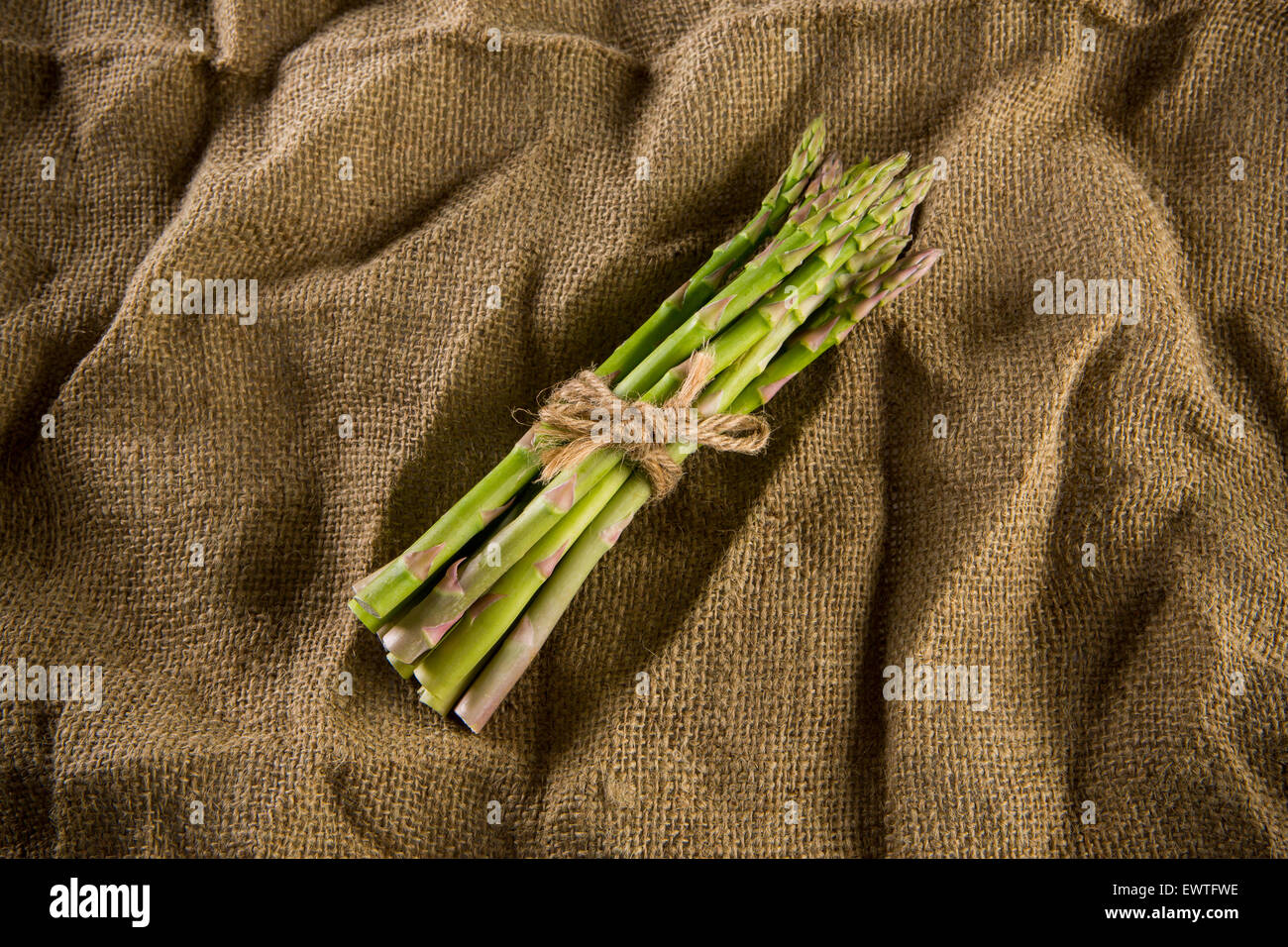A bunch of Asparagus on sackcloth. - Stock Image