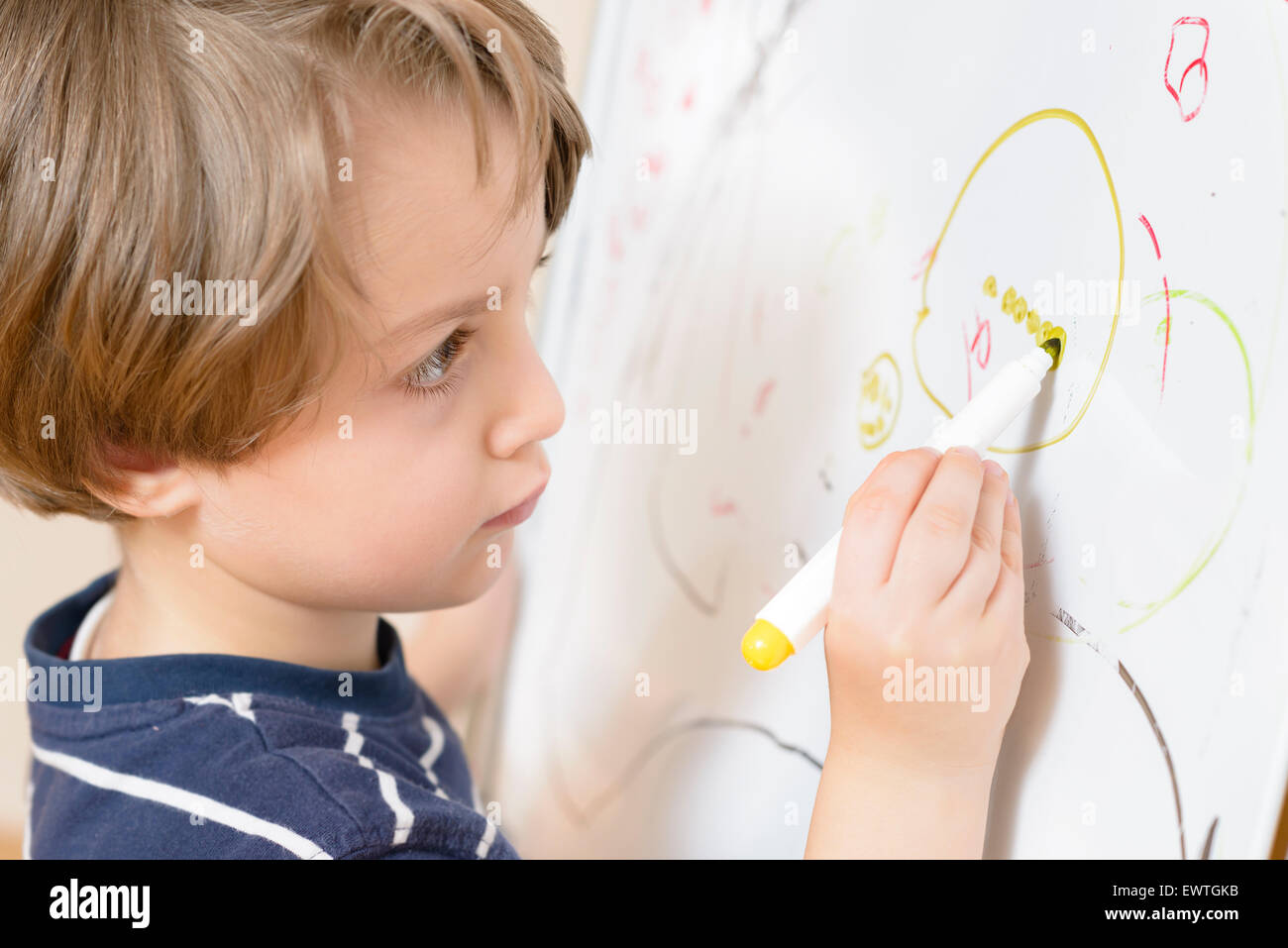 Cute boy drawing at kindergarten on a white board - Stock Image