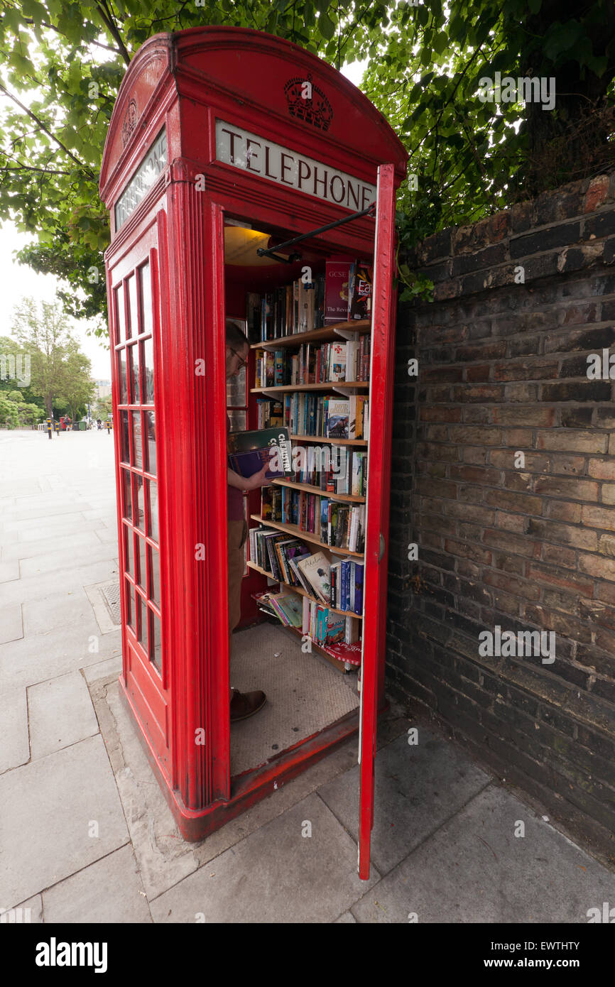 A man using  the Lewisham Micro Library, in an old, red, Telephone box, on Loampit Hill, Lewisham. - Stock Image