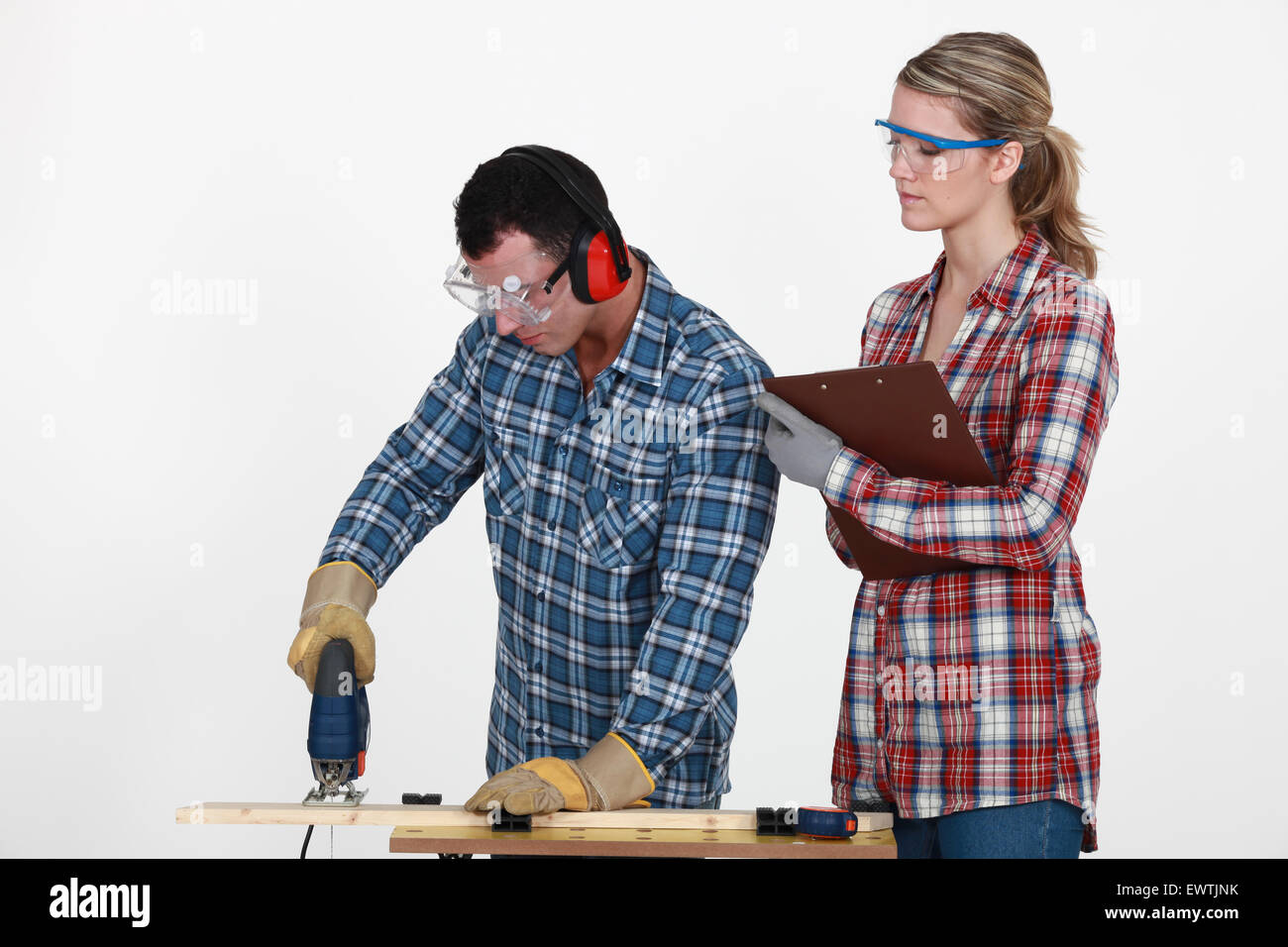 Man using band saw whilst woman supervises Stock Photo