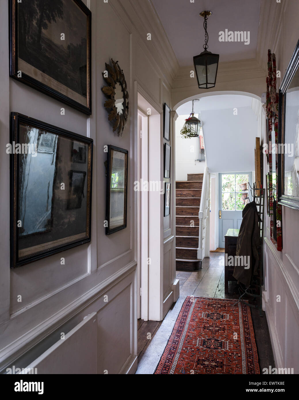 Townhouse entrance hall with framed landscape prints and red persian runner - Stock Image