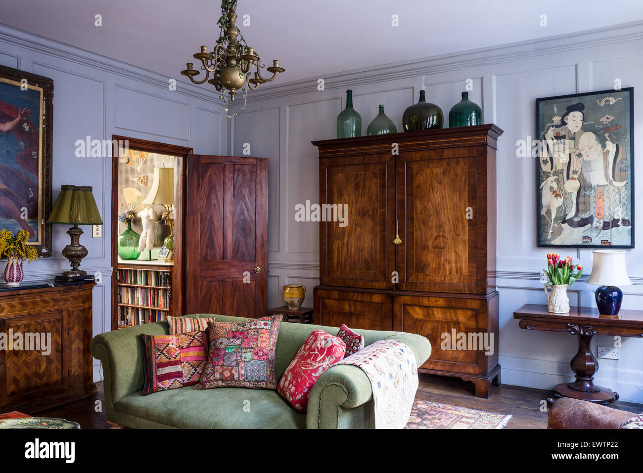 Indian And Antique French Cushions On Green Sofa In Living Room With Large  Antique Armoire And Oriental Artwork