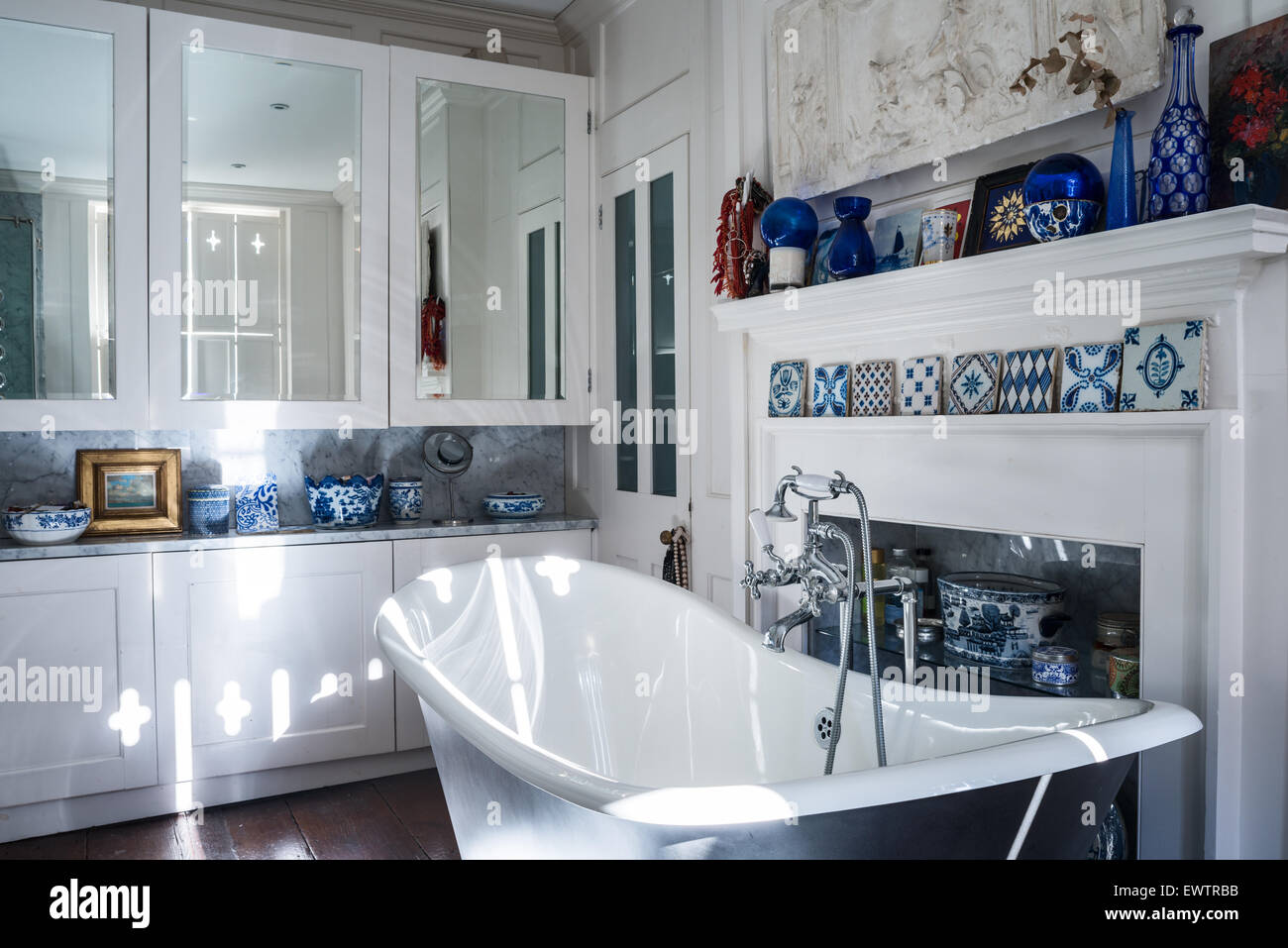 Blue and white decorative tiles on mantlepiece in bathroom with roll top bath from Albion Baths - Stock Image