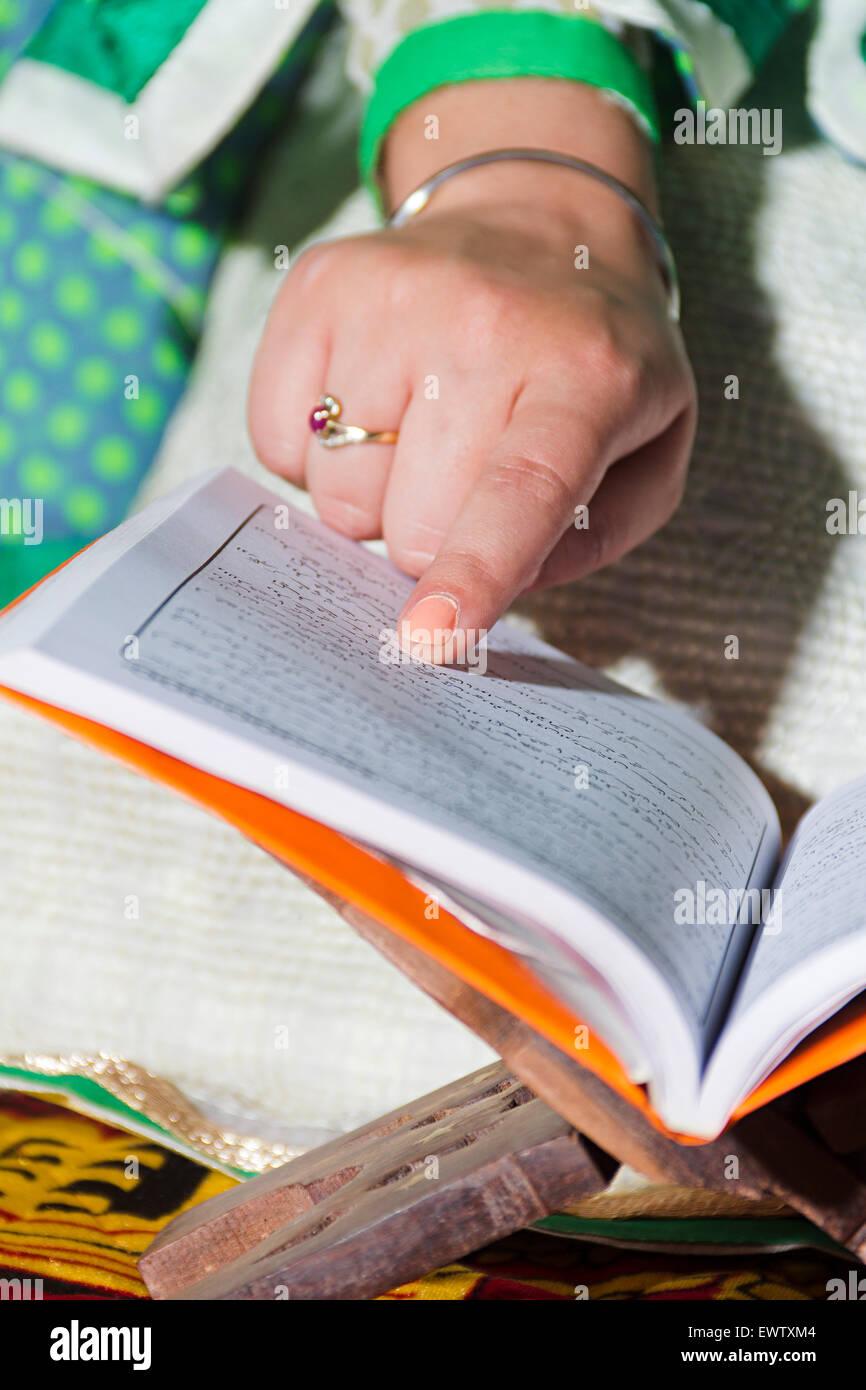 1 Muslim woman Reading Quran book - Stock Image