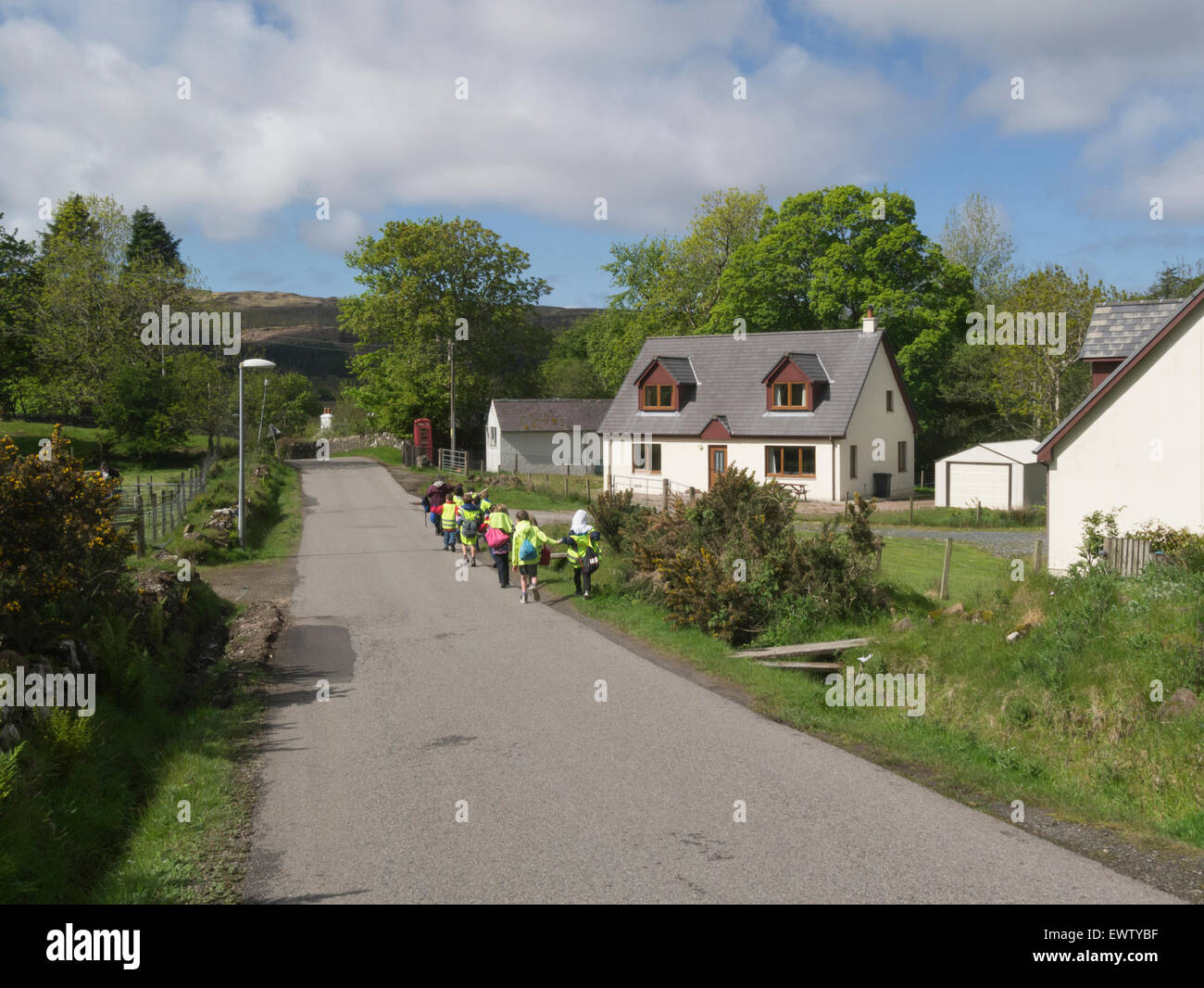 Schoolchildren wearing high visability jackets in walking train along narrow road Dervaig Isle of Mull Argyll and - Stock Image