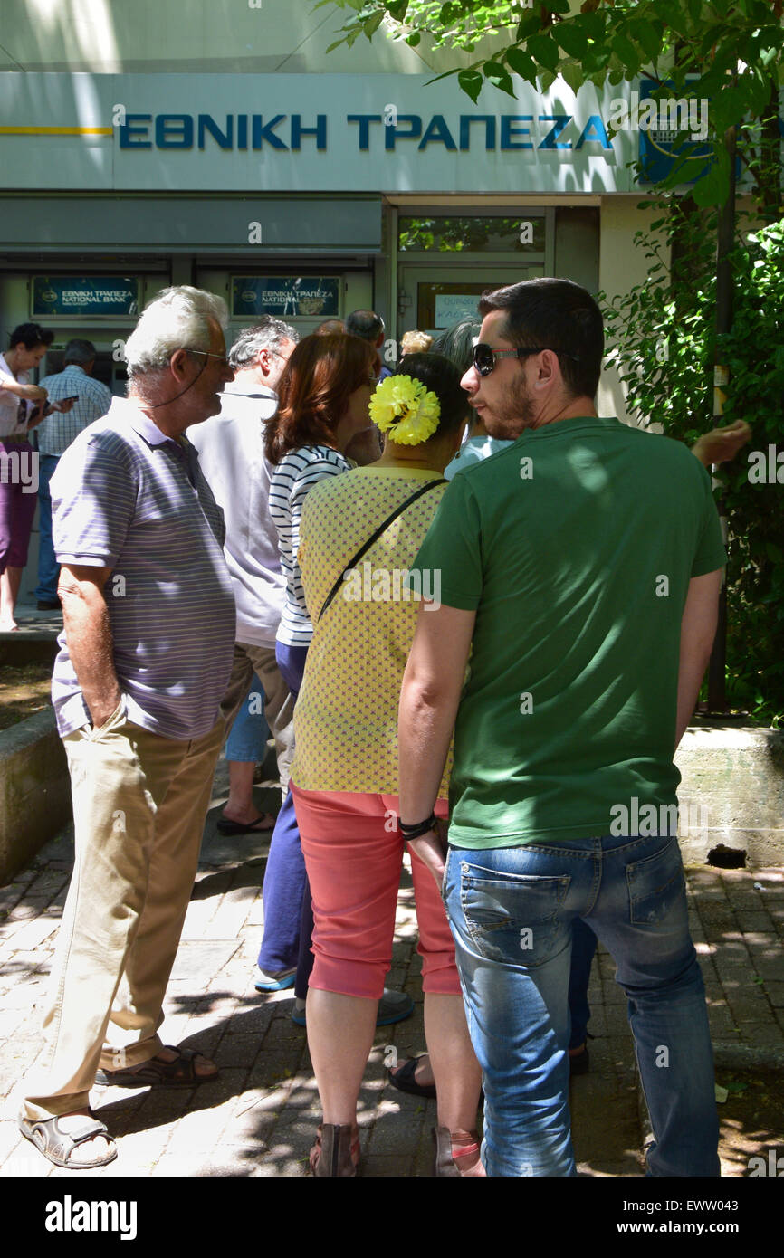 People queuing at bank branch to withdraw cash money from ATM machine cashpoint. Greek banks are closed to the public. - Stock Image