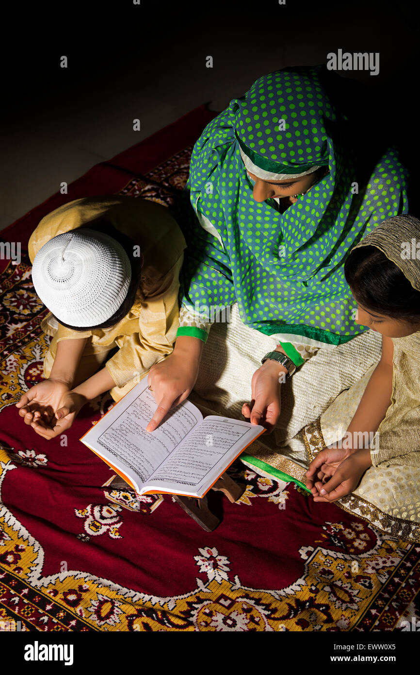 indian Muslim mother and kids reading Quran book - Stock Image