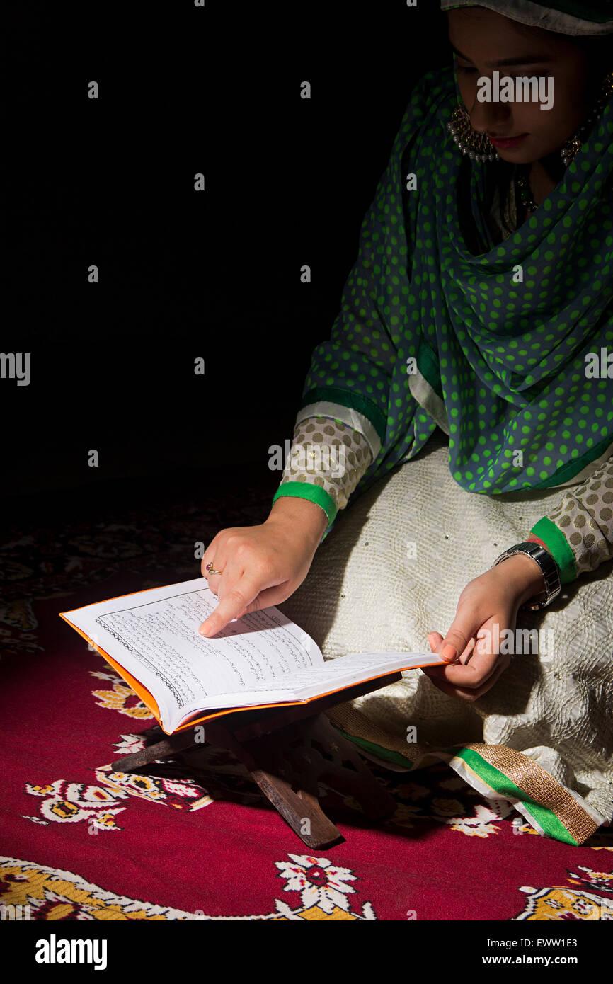 1 indian Muslim woman reading Quran book - Stock Image