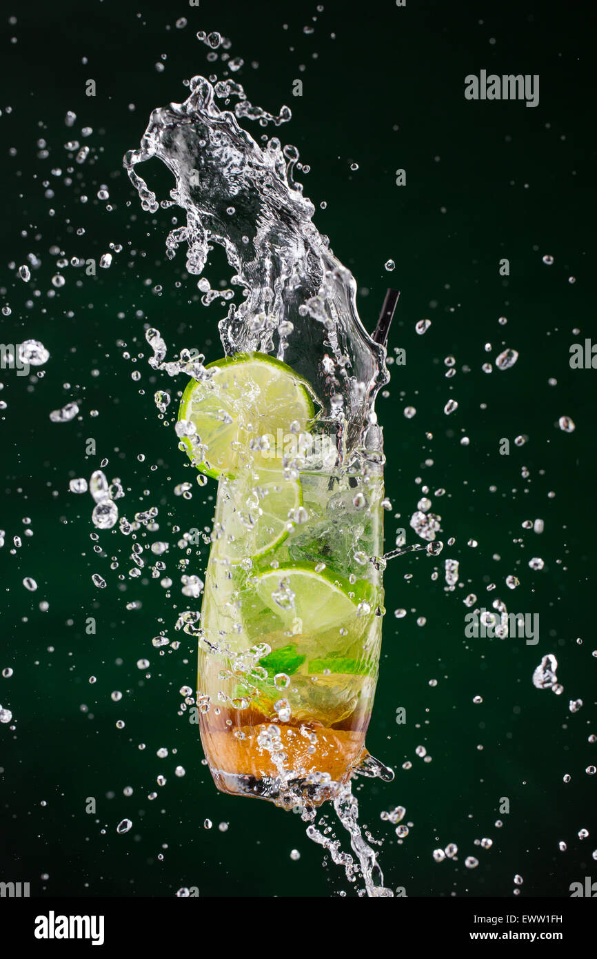 Mojito drink splashing out with dark background - Stock Image
