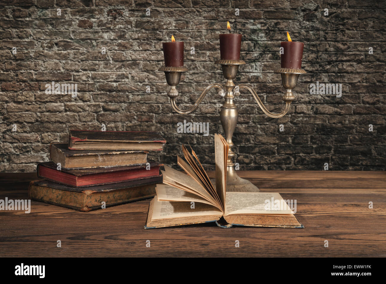 Old vintage books with candles in candlestick - Stock Image
